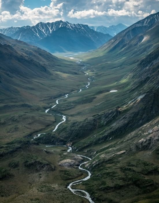an aerial image of a river cutting through a valley