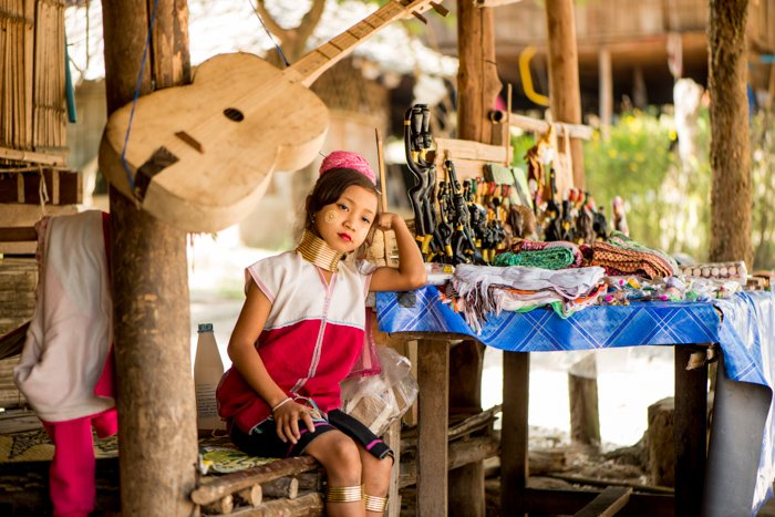 An environmental portrait photography shot of a young Kayan girl beside the table of trinkets she sells outside the family home