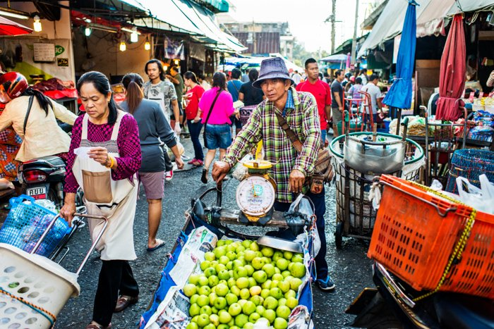 Environment portrait of a man selling apples in a market street in Chiang Mai