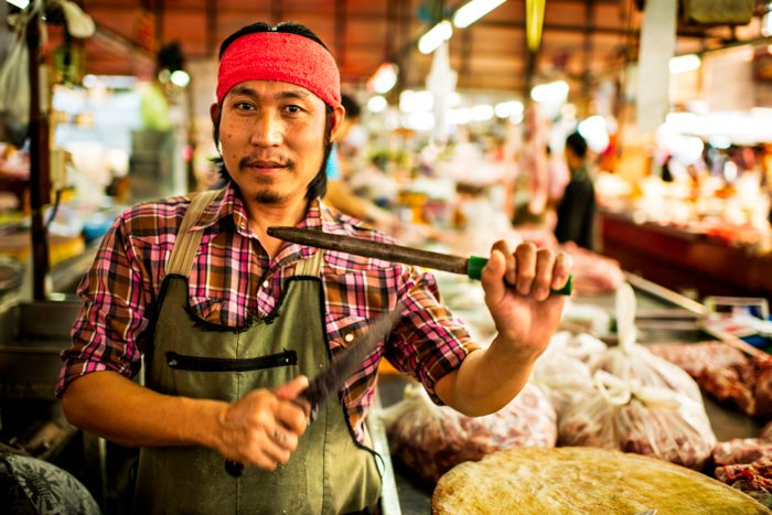 An environmental portrait photo of a market butcher holding knives up in Thailand