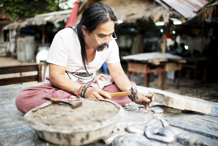 A man working with a hammer in an outdoor artist workshop in Thailand