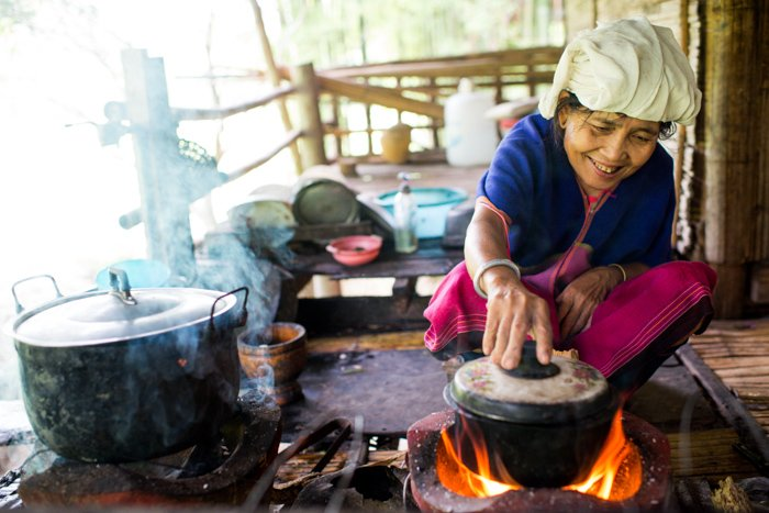 An environmental portrait of a Karen woman cooking on am outdoor patio with pots over a fire