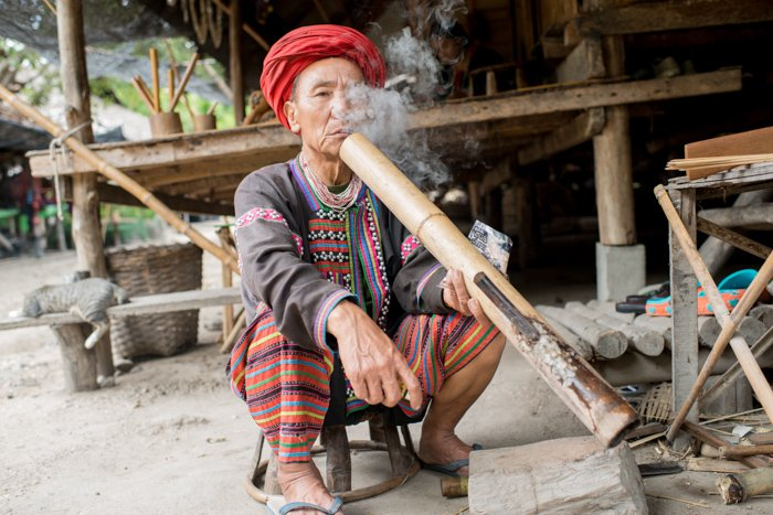 An environmental portrait of a Lahu man outside his house smoking long bamboo pipe