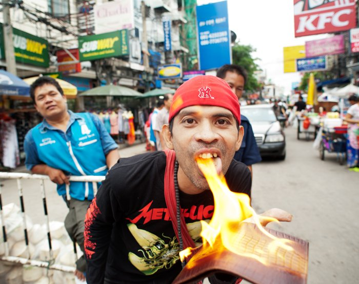 An environmental portrait photo of a street vendor in Bangkok demonstrating a fire-proof crocodile skin product
