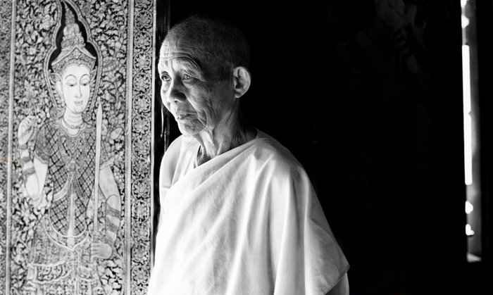 A black and white environmental portrait of a Buddhist nun with a carved relief in the background