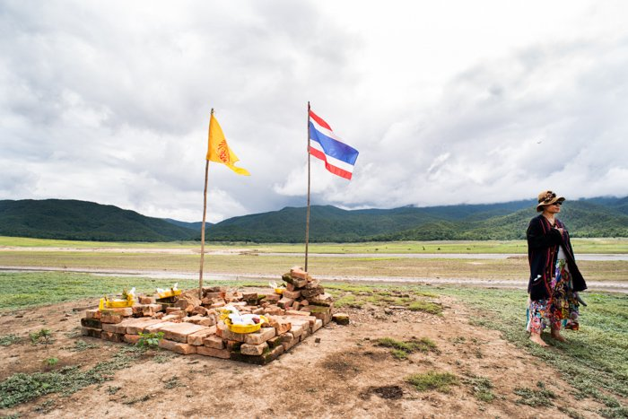 An environmental portrait of a woman standing beside a make shift Buddhist shrine in a a dry lake bed in Chiang Mai, Thailand