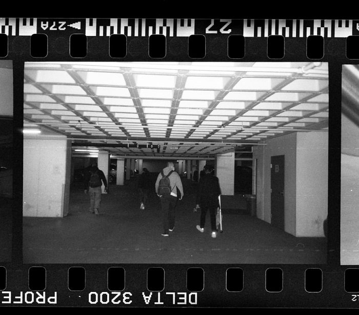 close-up of people walking in a car park taken on film