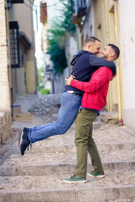 Engagement photography image of a gay couple in a fun and romantic moment in the street