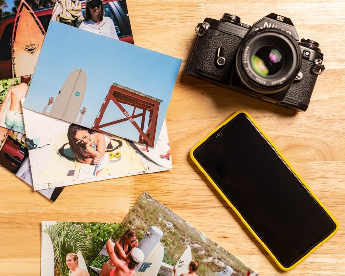 A flatlay image of a stack of photos, a phone, and a camera