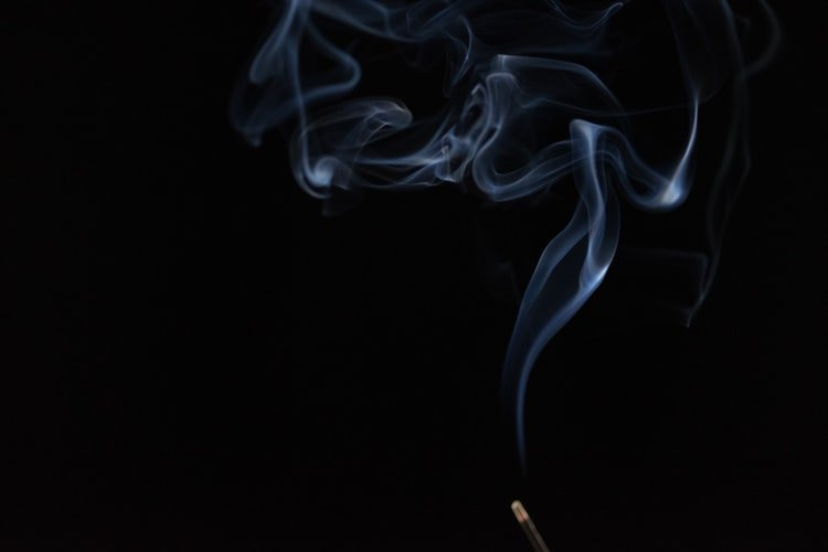 smoke from incense on a black background