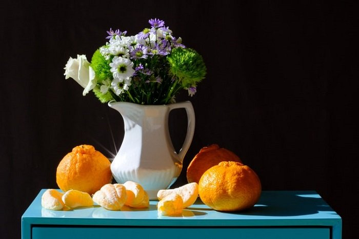 still life photo of flowers in a jug and oranges