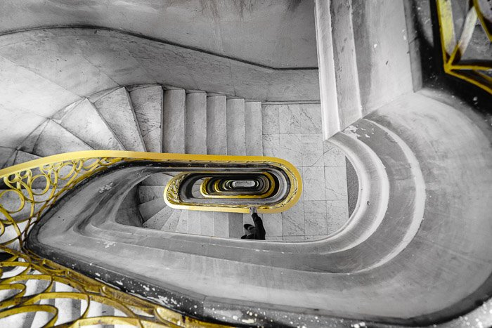 Image of a spiral staircase with a yellow bannister shot from above after photoshop selective color