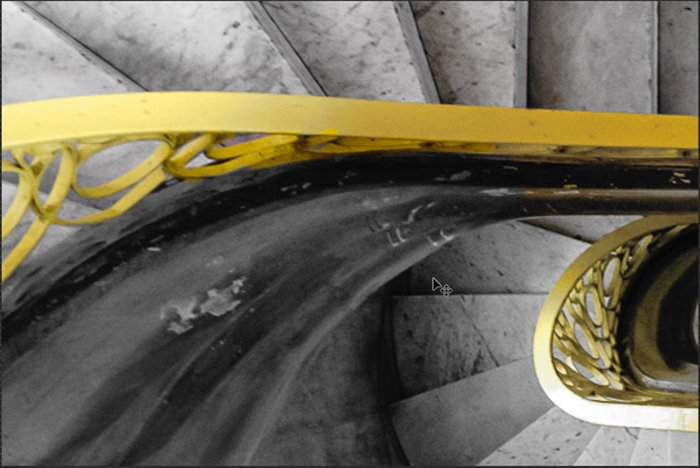 A detail of a spiral staircase with a brighter yellow bannister for Photoshop selective color process