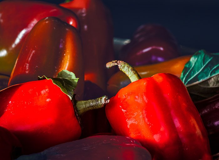 Bushels of red peppers bathed in sunlight at a farmer's market after photoshop selective color
