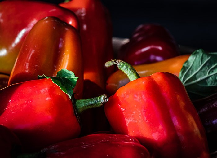 Bushels of red peppers bathed in sunlight at a farmer's market before photoshop selective color