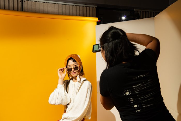 A female photographer taking photos of a model in a studio