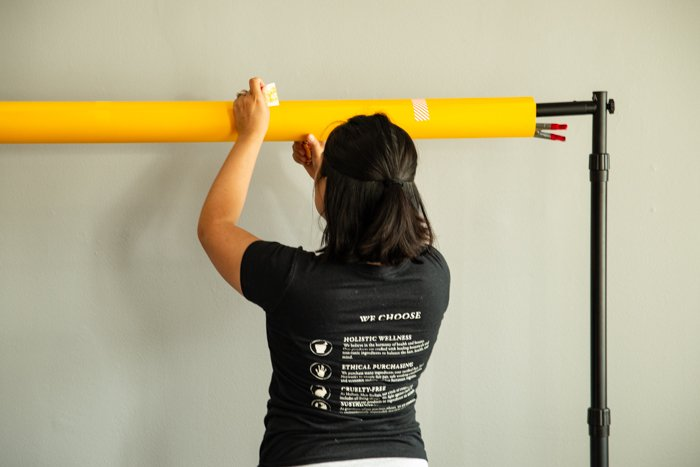 A woman setting up a background in the studio.