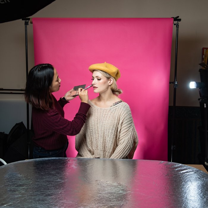 A woman applying makeup on a model in a small studio