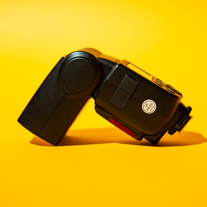 A speedlight against a yellow background