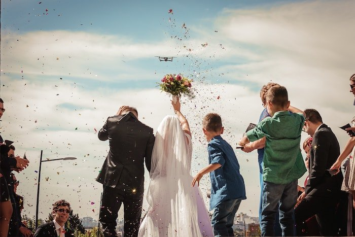 an image of a wedding being photographed by a drone