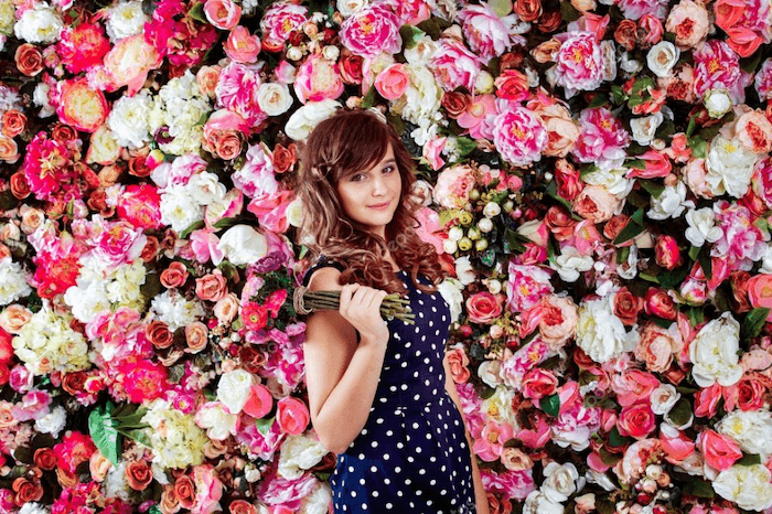 an image of a young woman holding a bouquet standing against a flower well