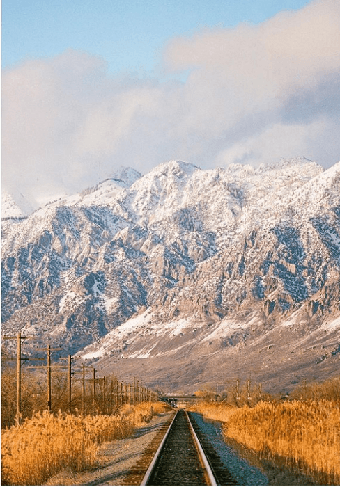 beautiful image of a train track leading to a snowy mountain range