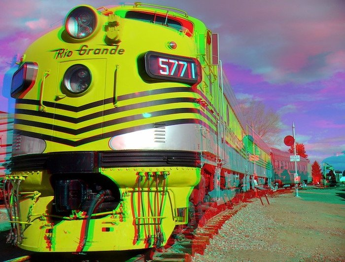 3D anaglyph photo of the front of a yellow train and its cars on tracks