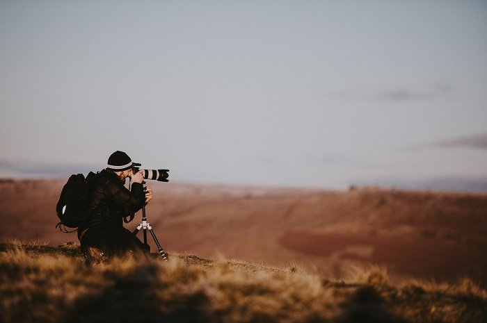 Photographer shooting outdoors over brown fields and a grey skey