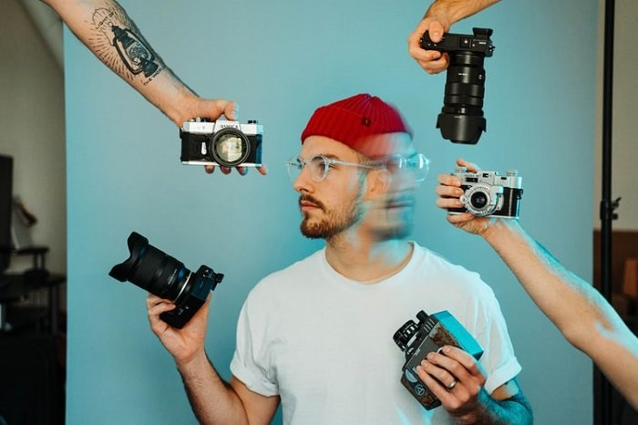 double exposure image of a model in a studio with several cameras held around him