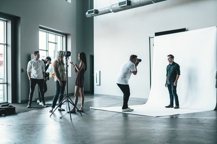 model posing in a studio in front a photographer