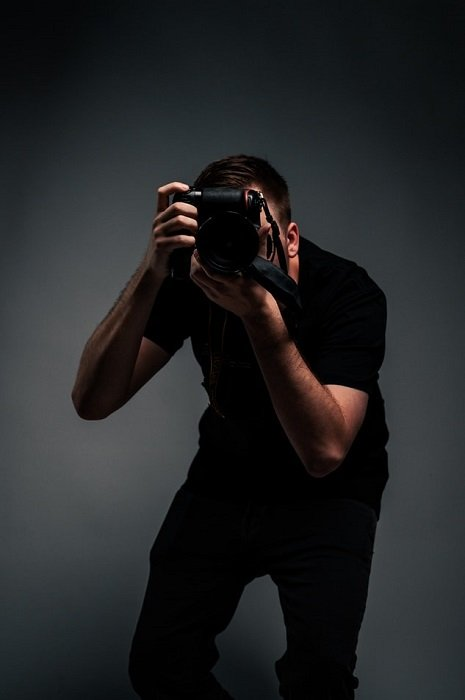 photographer facing the camera with a dark grey background