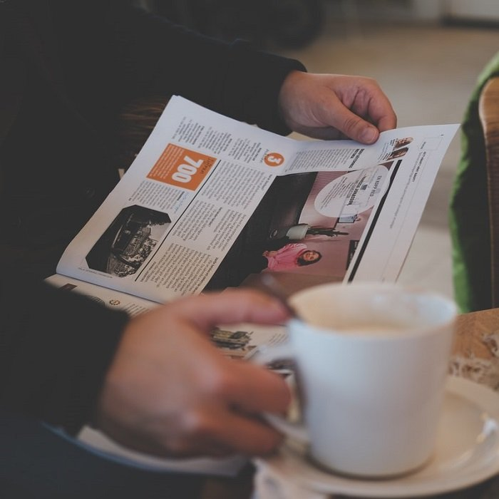 photograph of a person reading a local newspaper while holding a cup of coffee