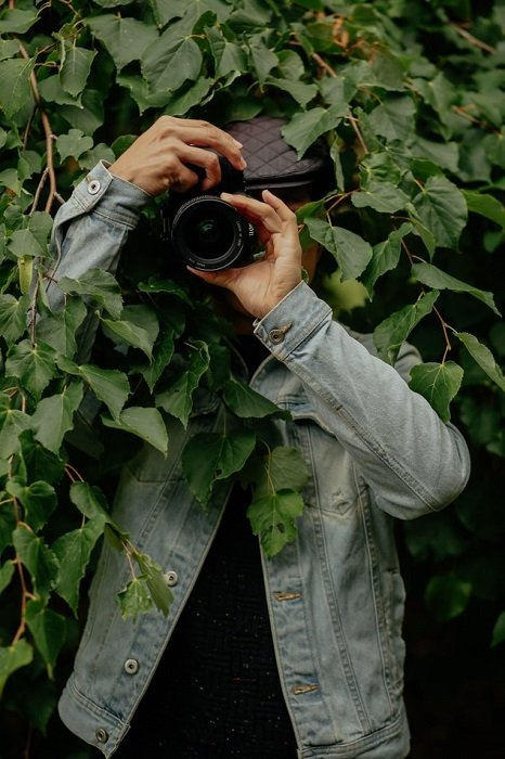 image of a photographer facing the camera while under leaves