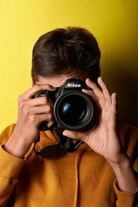 man shooting on a Nikon DSLR on a yellow background