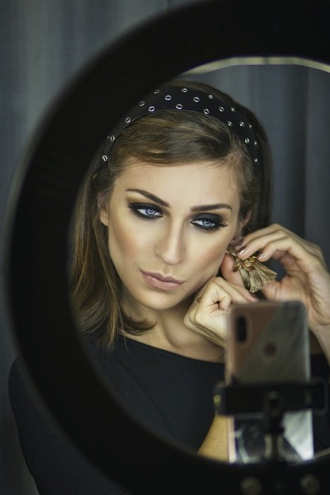 image of a female model taken from behind a ring light