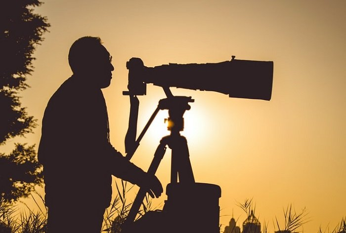 image of a man using a telephoto lens on a tripod with low sun in the background