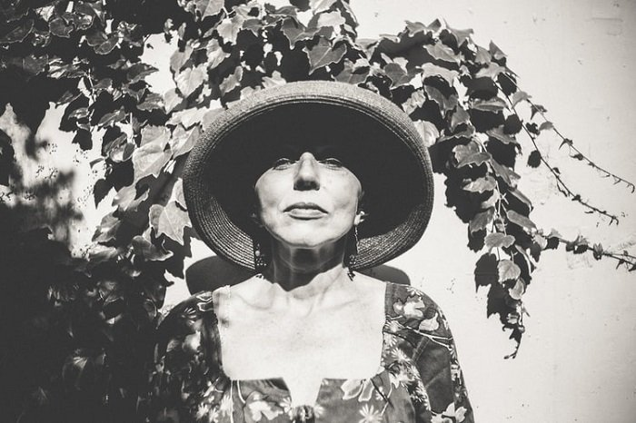 black and white film image of a woman wearing a hat and floral blouse