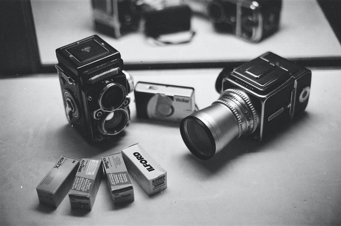 black and white image of a film camera with rolls of film