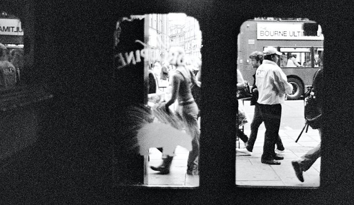 photograph of a busy street taken through the view of glass shop doors