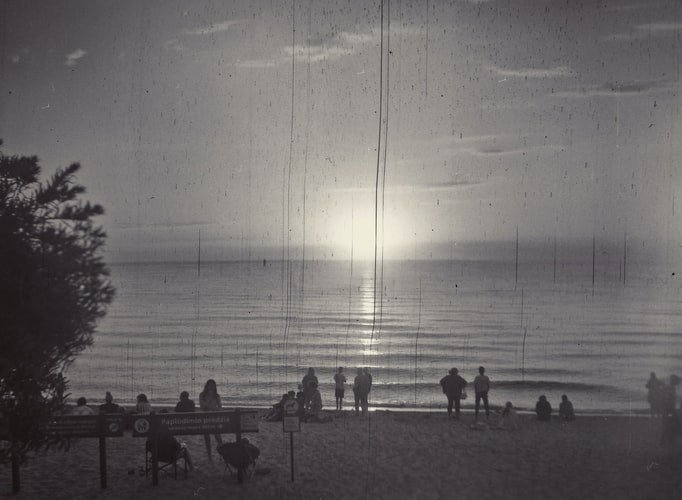 black and white photograph of the sun setting on a beach