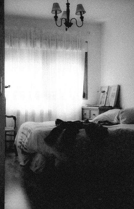 black and white photograph of a bedroom with high film grain