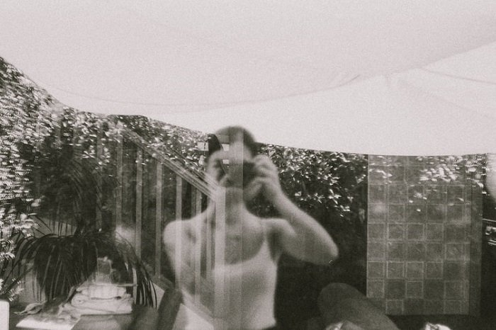 black and white films photograph of a window view with the photographer's reflection also showing