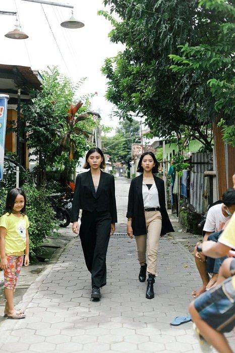 An editorial image of two fashion models walking down a residential neighbourhood sidewalk