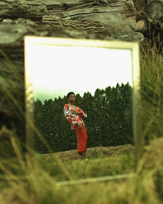 Editorial photo of a mirror with a reflection of a woman standing in nature with trees in the background