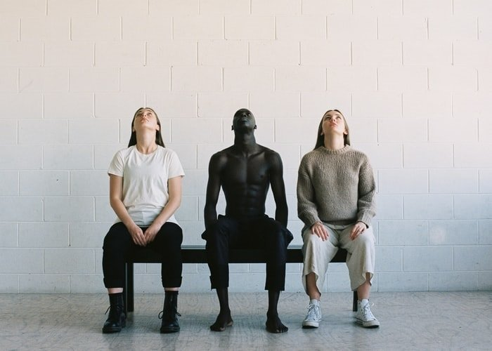 Editorial image of three people sitting on a bench and looking up with a white block cement wall behind them