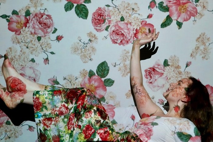 Studio image of a woman falling with a floral skirt, background, and projection for editorial style photography