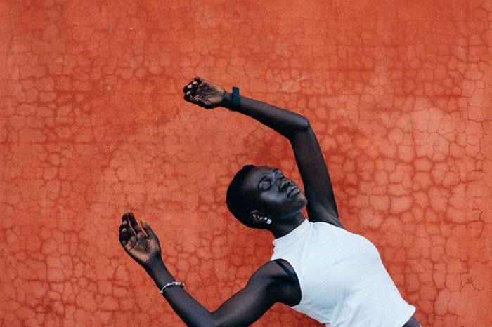 A conceptual editorial portrait of a woman falling back against an orange, textured background