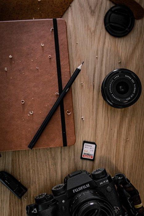 富士胶片镜头和相机,在木桌上放着笔记本和铅笔