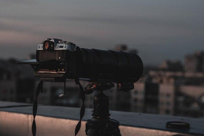 三脚架上有长焦镜头的照相机