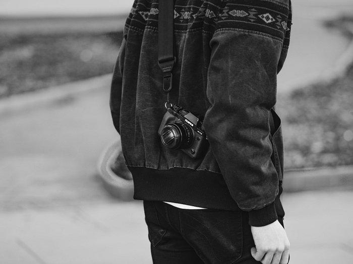 挂在男性肩膀上的富士胶片相机的黑白图像